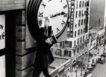 Harold Lloyd hanging from clock tower.